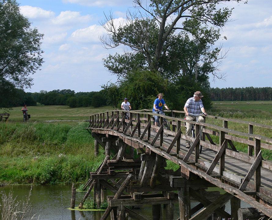 Radfahrer überqueren auf einer alten Holzbrücke die Seele