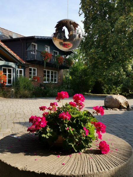 Geranienbepflanzter Mühlstein auf dem Ferienhof mit Blick auf den Steinbrunnen